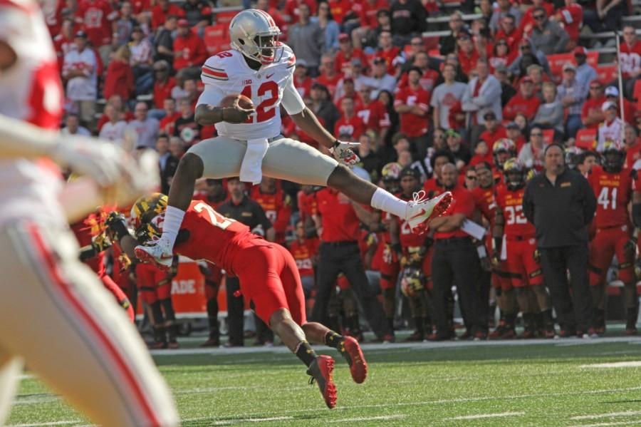 OSU Quarterback Cardale Jones hurdles over a defender.  Jones led the Bucks to a 59-0 win against Wisconsin in the Big 10 Championship Game.