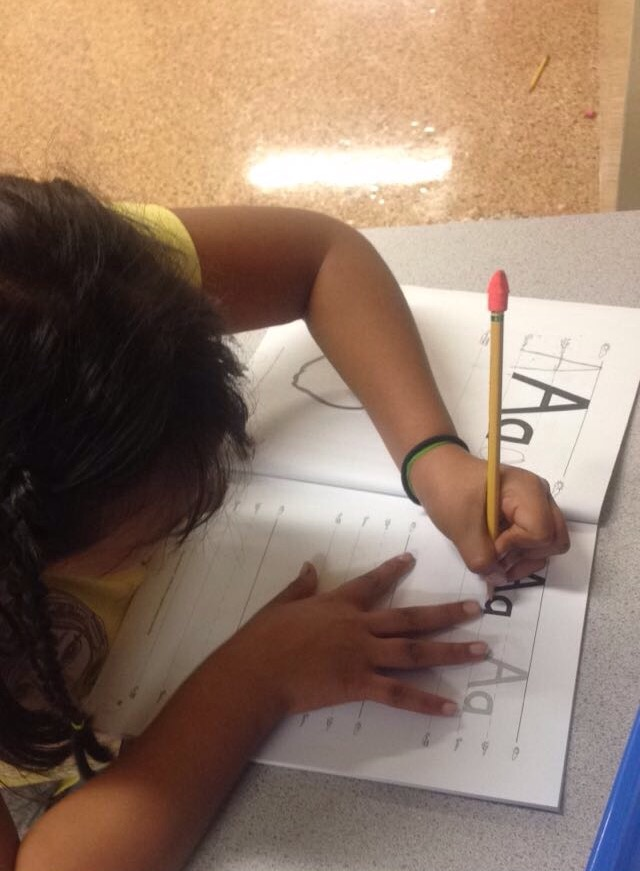 Student at Colonial Hills practicing how to write the ABC's in English.