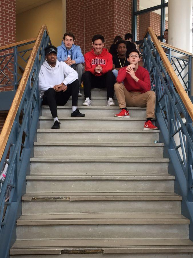 Journalism students pose for photos on lunch room steps.