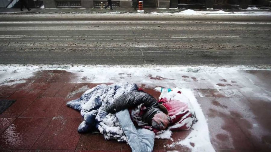 Homeless man sleeps bundled in blanket on the ground while snow falls.