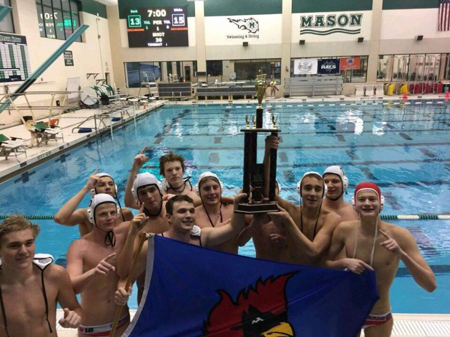 Members of the Boys Water Polo team hold up their trophy for winning states.