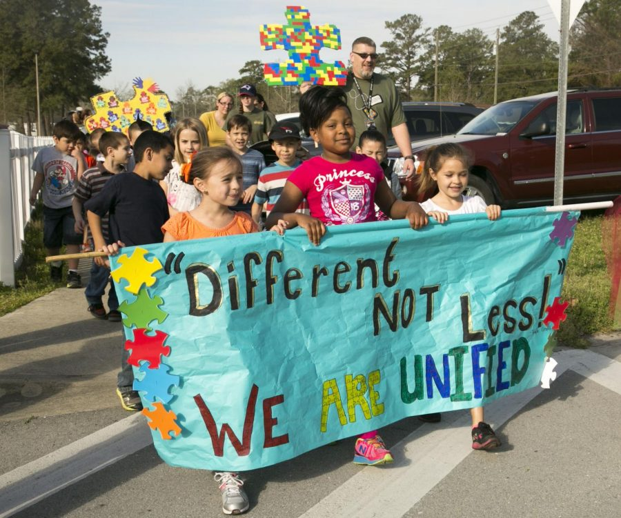 Families  aboard Marine  Corps Base Camp Lejeune walk and hold banners in support of autism awareness