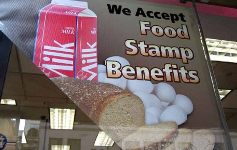 Taken in 2007, a grocery store hangs up a sign in their windows saying they accept food stamp benefits. If Trump's new policy goes into effect, many Americans will be unable to use their food stamps to buy food in grocery stores.
